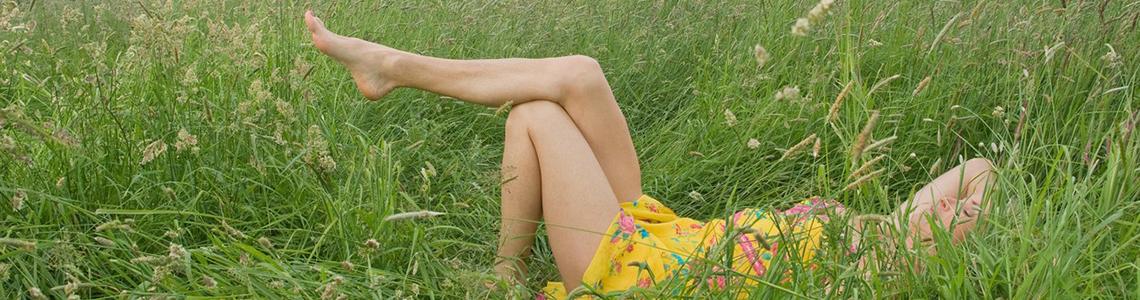 Fußpflegegeräte für wohltuende und gesunde Füße wie von dieser Dame auf einer Wiese