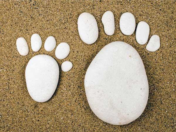 Große und kleine Füße aus Steinen gelegt